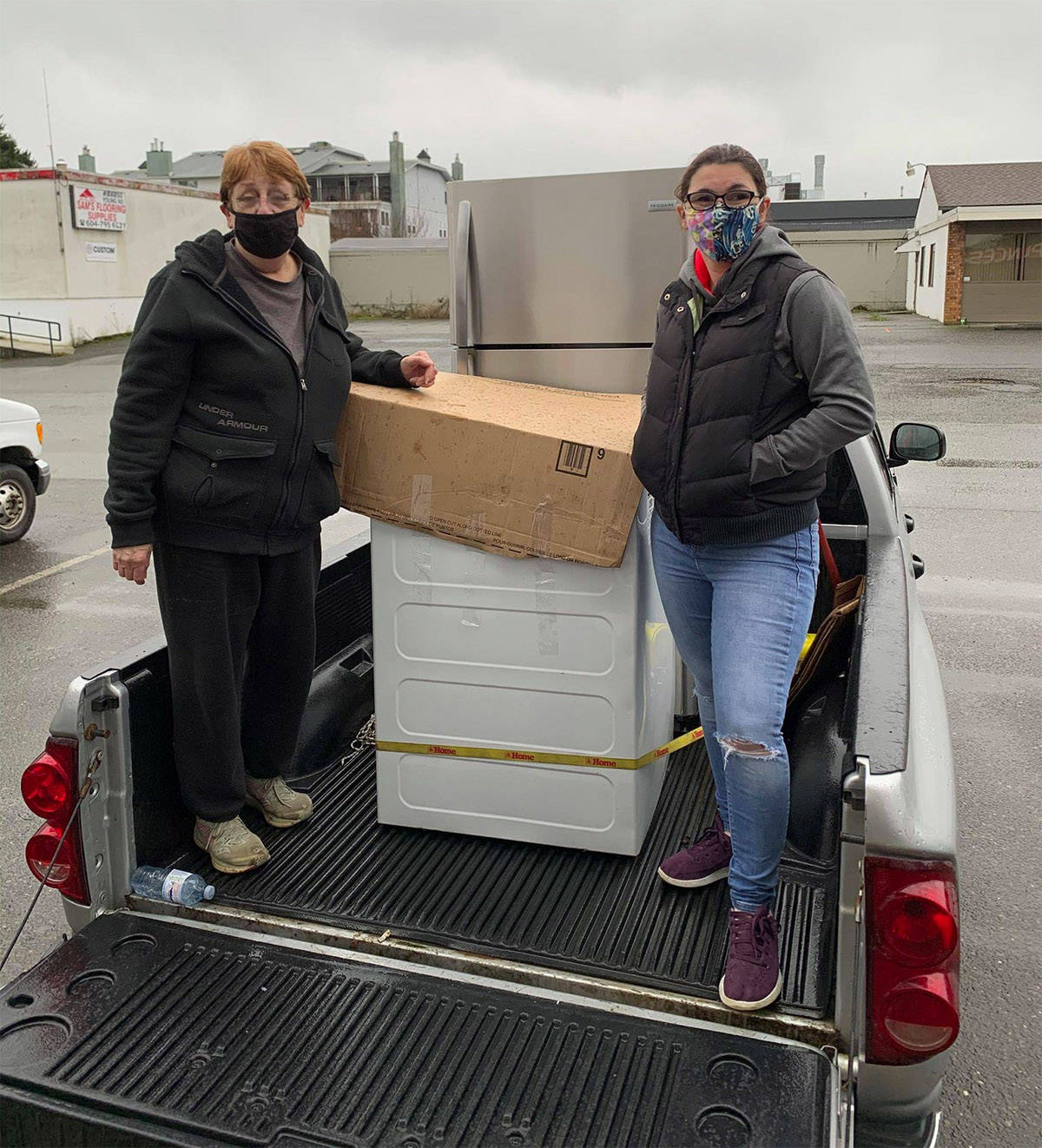 Sue Knudsen (left) and Trisha Mercer stand in the back of a pickup truck with the appliances that were delivered to a family in need on Saturday, Jan. 2, 2020. (Submitted)